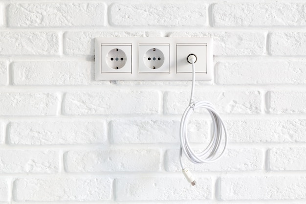 Row of power and tv sockets and tv cable on brick wall