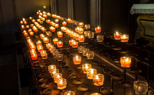 Row of red candle lights at altar in cathedral