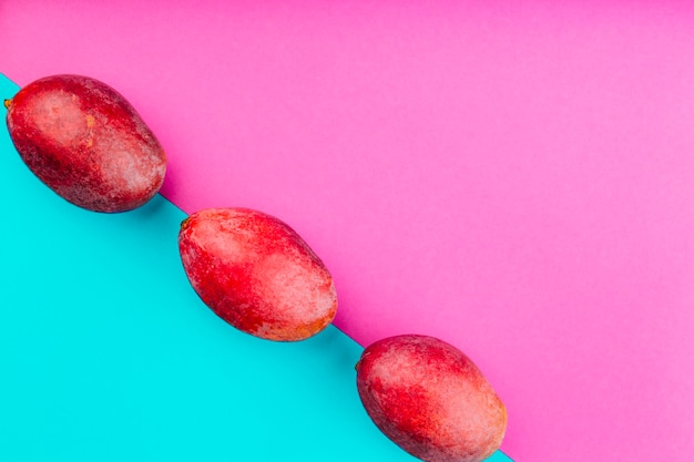Row of red mangoes on dual pink and blue background