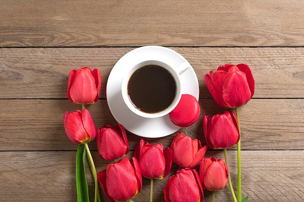 Row of red tulips and cup of black coffee americano on wooden background flat lay