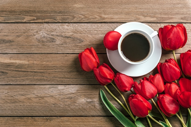 Row of red tulips and cup of black coffee americano on wooden background
