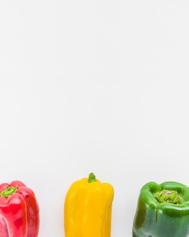 Row of red; yellow and green bell peppers on white backdrop