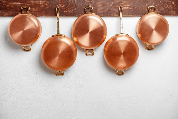 Row of shiny clean copper pans hung on wooden plank
