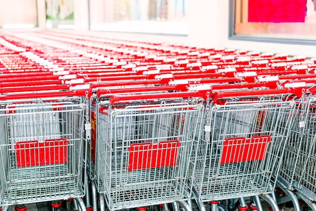Row of shopping carts with red handles on evening blurry background near entrance of supermarket in winter