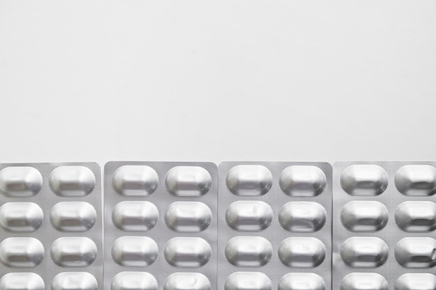 Row of silver blister pack pills isolated on white background