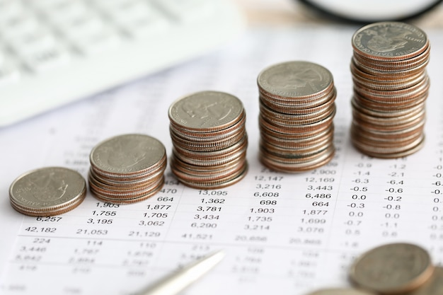 Row of silver coins standing at financial report paper