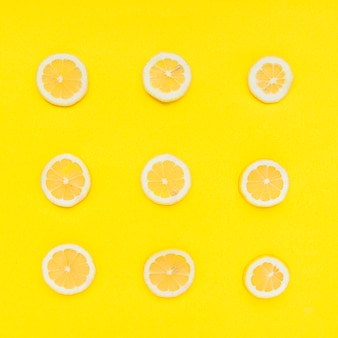 Row of sliced citrus fruits on yellow background