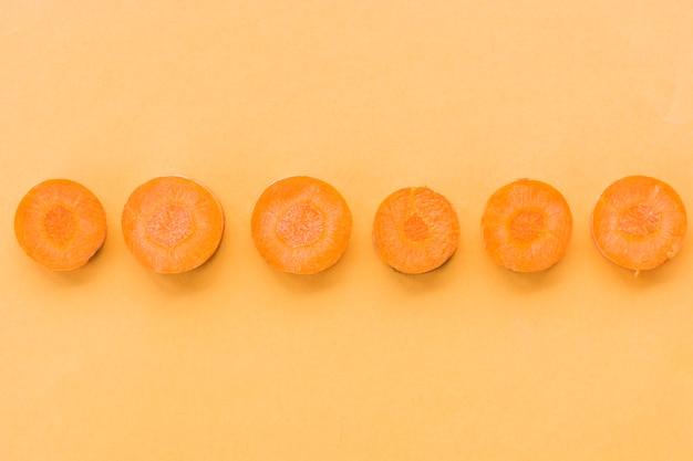 Row of sliced fresh carrots on orange background