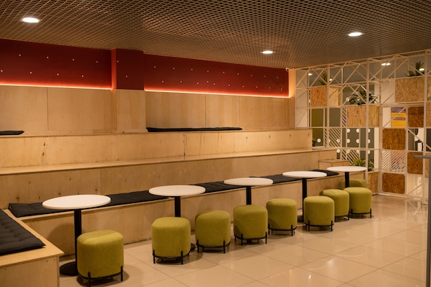 Row of soft velvet chairs by white small round tables inside modern cafe in college or university
