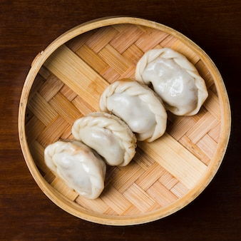 Row of steamed dumplings dim sum in bamboo steamer on table