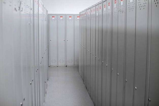 A row of steel grey lockers along the white wall.