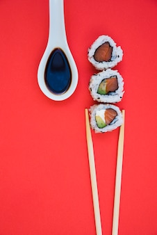 Row of sushi rolls with chopsticks and soya sauce in white spoon over red backdrop