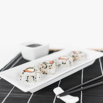 Row of sushi on white tray with chopsticks