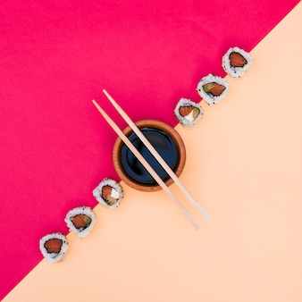 Row of sushi with soya sauce in bowl with chopsticks on pink and yellow dual backdrop