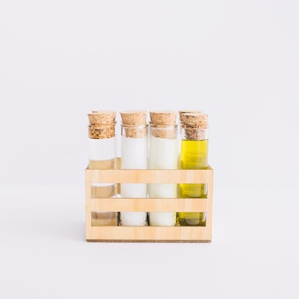 Row of test tubes with spa products in wooden container on white background
