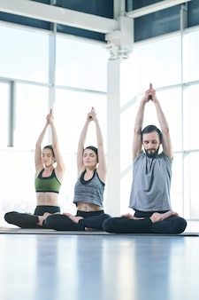 Row of three active people in sportswear sitting on mats with crossed legs and arms raised over heads while keeping balance