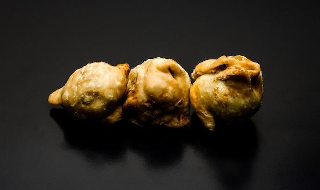 A row of three fried samosas on a textured dark background