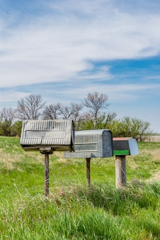A row of three old metal farmers mailboxes on the prairies in rural saskatchewan, canada