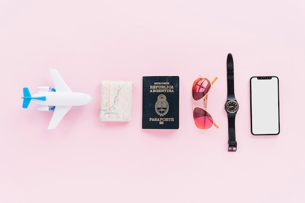 Row of toy airplane; folded map; passport; sunglasses; wrist watch and smartphone on pink background