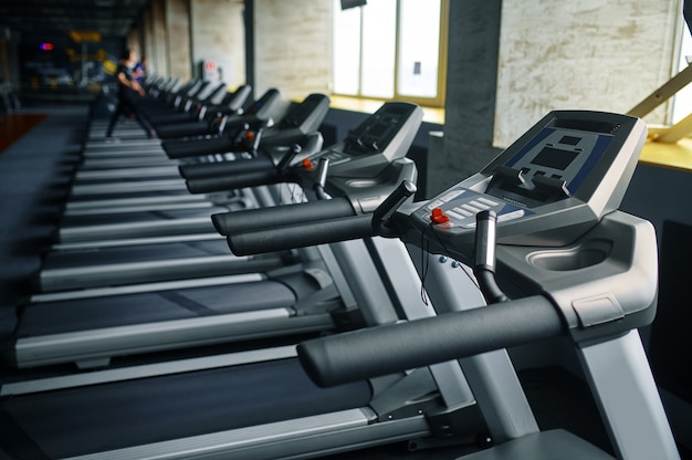 Row of treadmills in gym, running machine, nobody. equipment for cardio trainings and health care, sport club interior