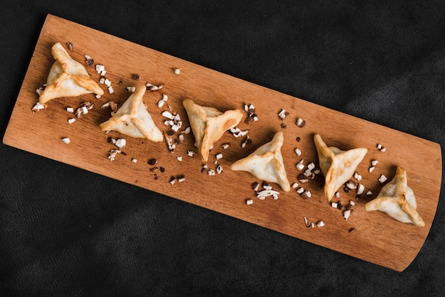 Row of triangular dumpling on wooden tray against black textured backdrop
