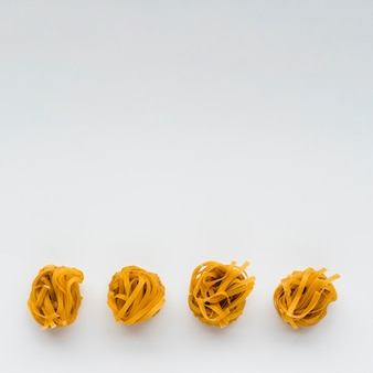 Row of uncooked tagliatelle pasta at the bottom of white background