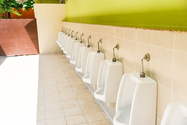 Row of urinal toilet blocks for man on tiled wall