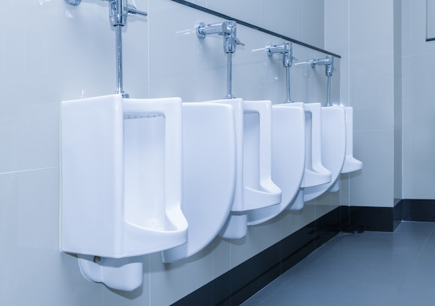 Row of urinal toilet blocks in public restroom