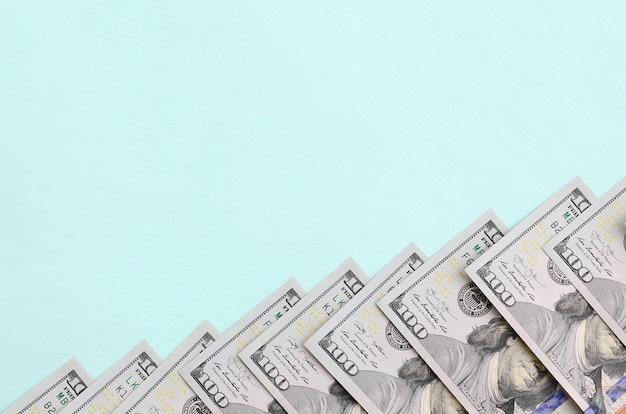 Row of a us dollar bills of a new design lies on a light blue
