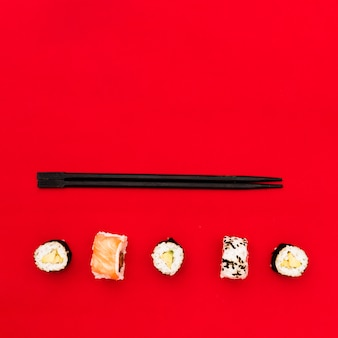 Row of various asian rolls over red surface with black chopsticks