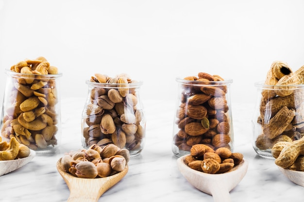 Row of various fresh nut food in spoon and glass jar
