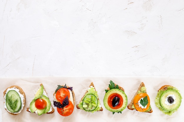 Row of vegetarian sandwiches on white background.