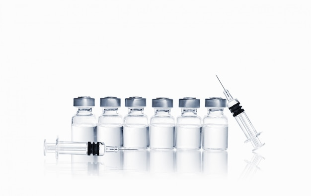 Row of vials with medication and syringe with needle for injection on white background