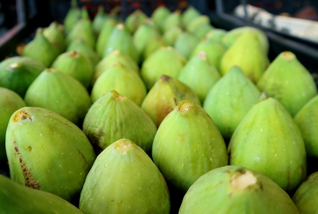 Row of vibrant green fresh ripe figs at the local market