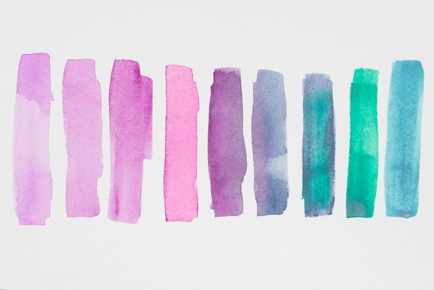 Row of violet and blue paints on white paper