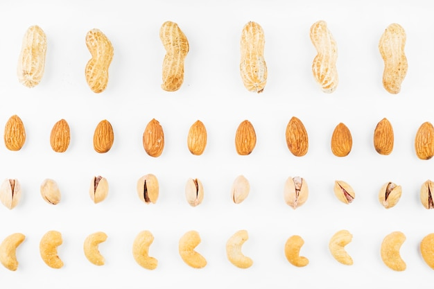 Row of walnuts; peanuts; almonds; pistachios and cashew nuts on white background