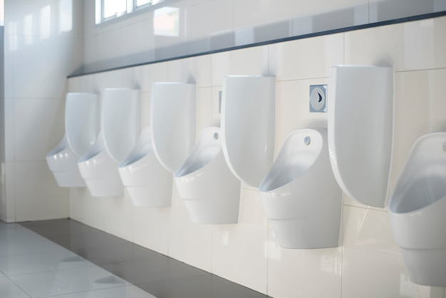 A row of white ceramic urinals for men in restroom.