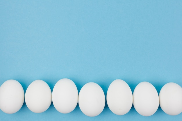 Row of white chicken eggs on blue table