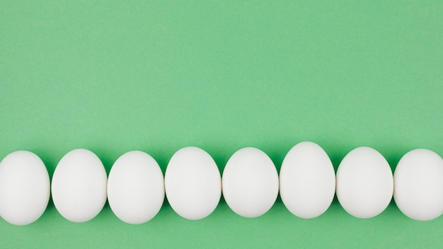Row of white chicken eggs on green table