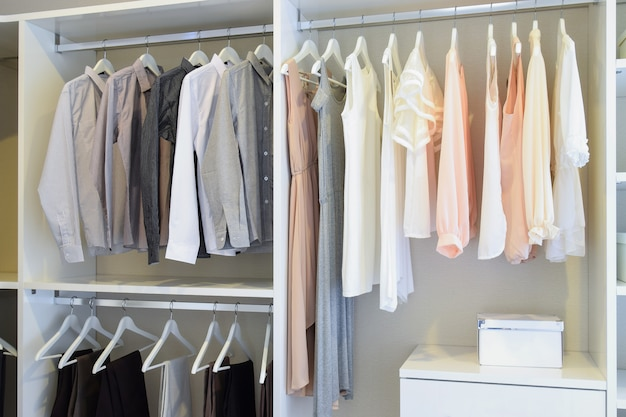 Row of white dress and shirts hanging in white wardrobe
