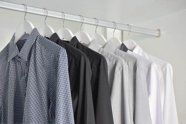 Row of white, gray, black shirts hanging in wooden wardrobe