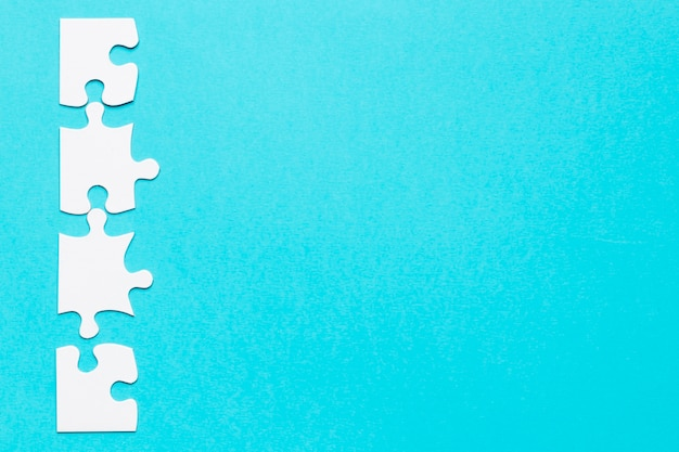 Row of white jigsaw puzzle on blue backdrop