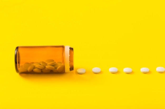 Row of white pills in front of open glass bottle over the yellow backdrop
