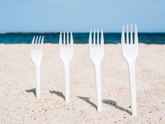 Row of white plastic forks stuck in sand on beach