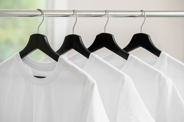 Row of white t-shirts on hangers hanging on rack