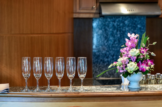 Row of wine glass with flower decoration on marble bar