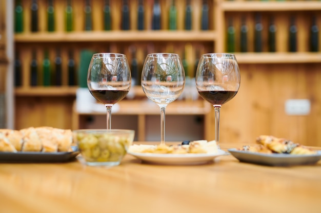 Row of wineglasses with red wine and snacks near by prepared for sommelier in the cellar of restaurant