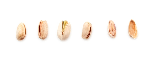 Row with kind of pistachios isolated on white. set of pistache, top view
