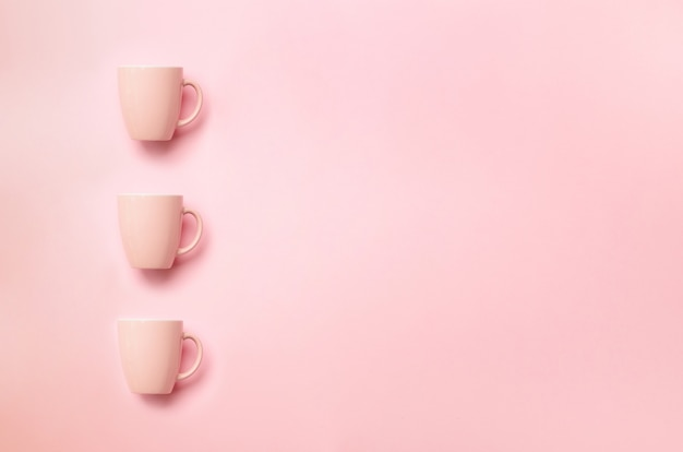 パンチのある背景の上のピンクのカップを持つ行。誕生日パーティーのお祝い、ベビーシャワーのコンセプト。ミニマリストスタイルのデザイン