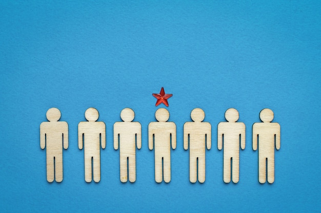 A row of wooden men and one leader marked with a star. the concept of the head.